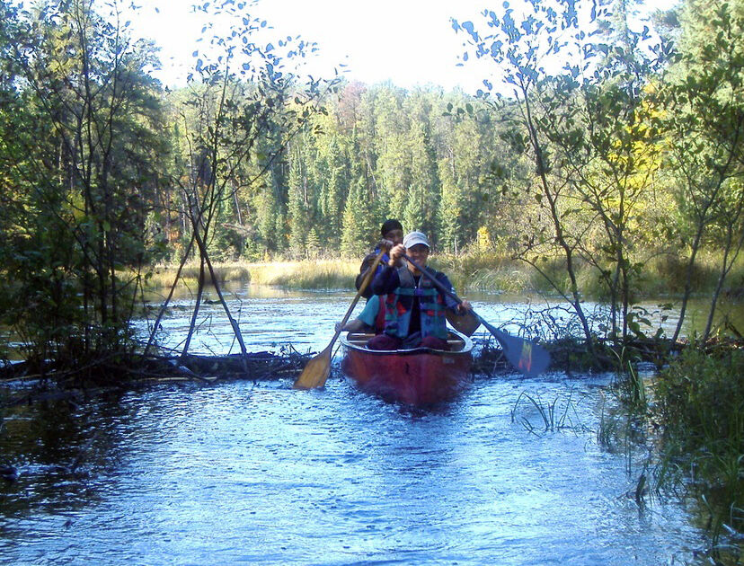 3 students canoeing in creek