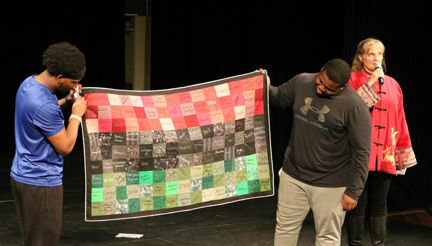 Students holding quilt